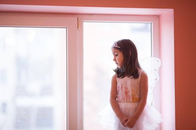 Niña-mariposa en un tutú blanco bailando jugando en el alféizar de la ventana