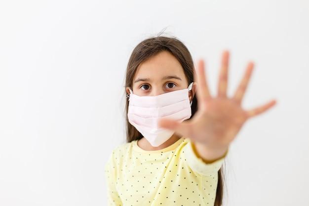 Niña en una máscara desechable sobre un fondo claro. protección epidémica del virus corona
