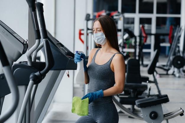 La niña de la máscara desinfectando el equipo del gimnasio durante una pandemia.