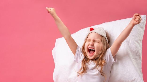 Niña en una máscara para dormir está acostada sobre una almohada, bostezando y estirando