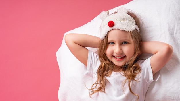 Niña en una máscara para dormir está acostada sobre una almohada con las manos detrás de la cabeza