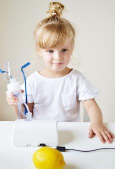 Niña en una máscara para inhalaciones, haciendo inhalación con nebulizador en casa inhalador sobre la mesa, niño enfermo interior