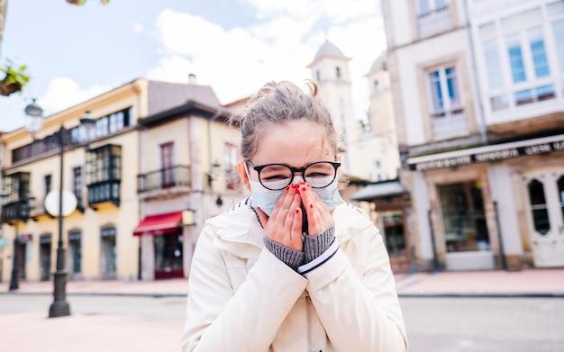 Una niña con una máscara se lleva las manos a la cara en medio de una ciudad