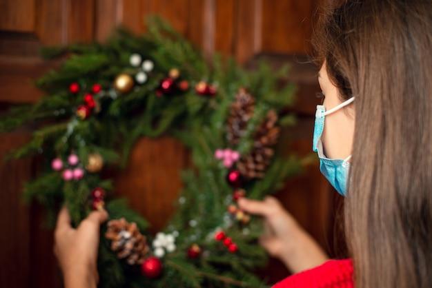 Niña en máscara médica colgando de la corona de navidad en la puerta