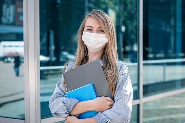 Una niña con una máscara médica se encuentra debajo del edificio de un centro de negocios.