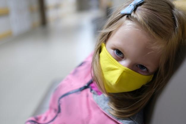 Niña en máscara médica protectora amarilla sentada en el pasillo del hospital