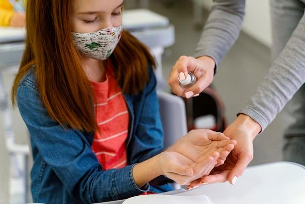Niña con máscara médica recibiendo desinfectante de manos del maestro