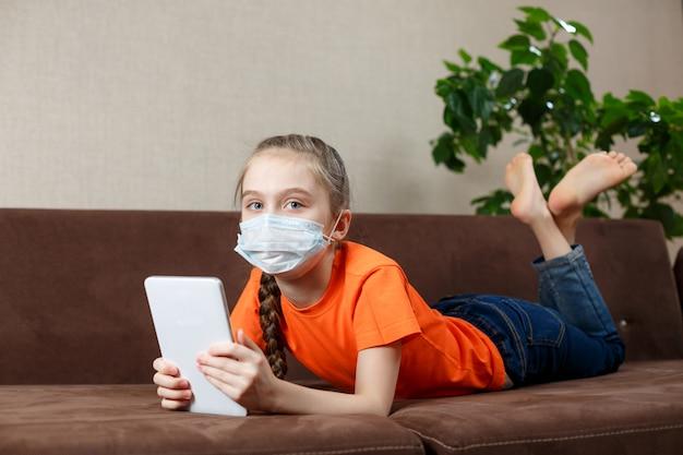Niña en máscara médica tumbado en el sofá y con tablet pc. aislamiento en casa. mirando a la cámara