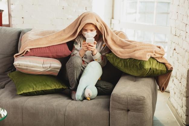 Niña con máscara protectora aislada en casa con síntomas respiratorios de coronavirus como fiebre, dolor de cabeza, tos en estado leve. cuidado de la salud, medicina, cuarentena, concepto de tratamiento. se siente enfermo.