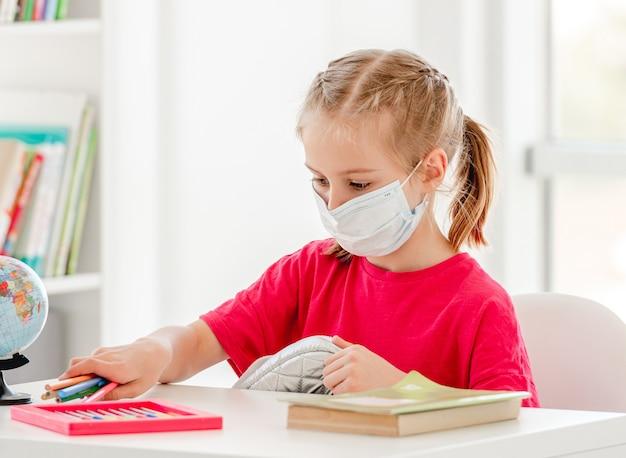 Niña con máscara protectora en la lección de la escuela en el aula brillante