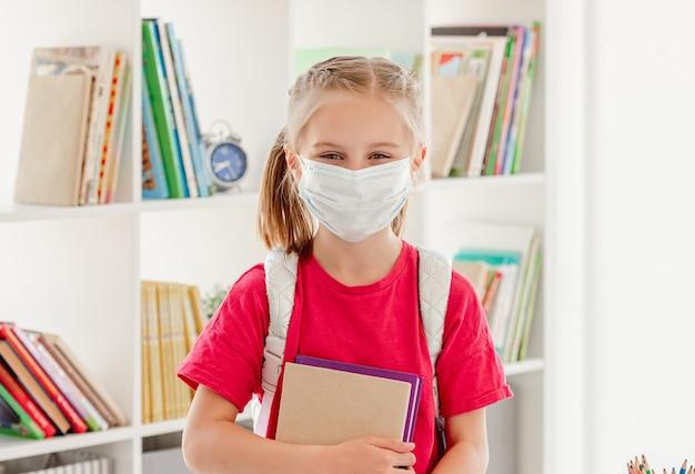 Niña con máscara protectora con mochila y ábaco en la escuela