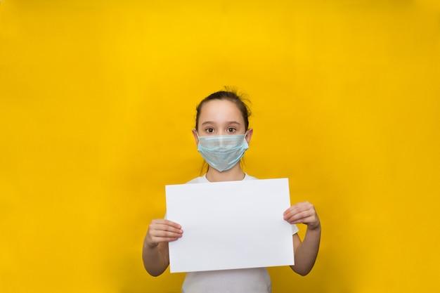 Niña en una máscara protectora sostiene una hoja de papel en blanco en una pared amarilla. protección contra coronavirus