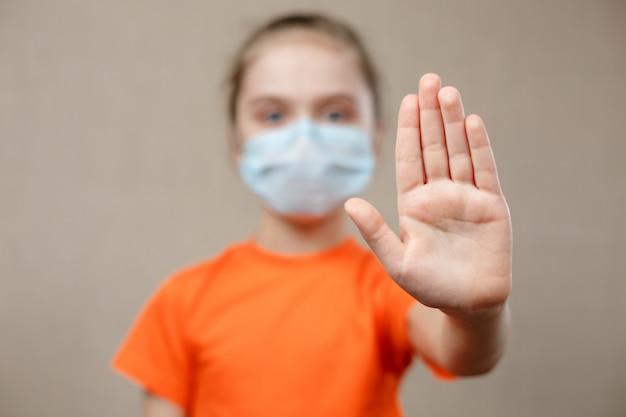 Niña con máscara para proteger. mostrando señal de stop. detener el virus y las enfermedades epidémicas. coronavirus covid-19. quédese en casa y manténgase seguro. enfoque selectivo en mano.