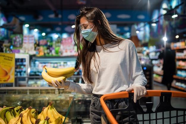 La niña con mascarilla quirúrgica va a comprar plátanos.
