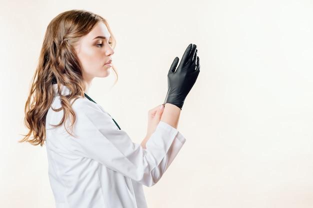 Niña un médico sobre un fondo claro en guantes negros