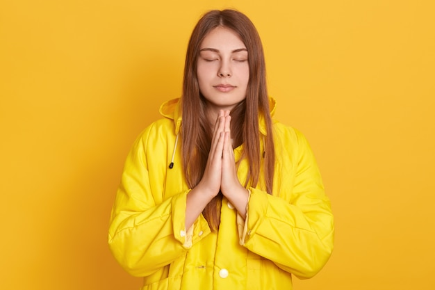 Niña meditando o rezando en la pared amarilla