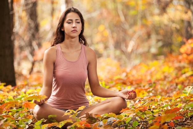 Niña meditando en el parque otoño