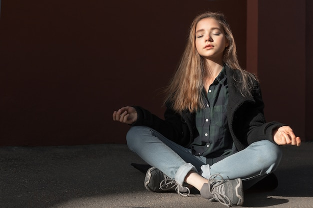Una niña meditando y respirando plantean loto en tiempo soleado. consiguiendo armonía interior y salud.