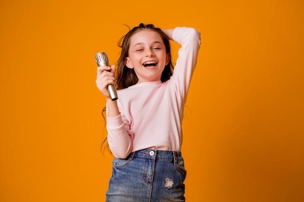 Niña con micrófono sonriendo cantando