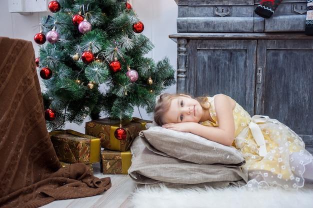 La niña miente en las almohadas en un vestido amarillo, navidad.