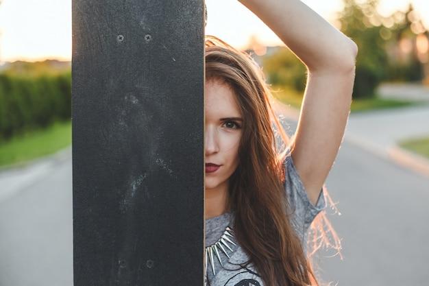 Una niña mira fuera del skateboard. retrato al aire libre con estilo de una hermosa niña morena.
