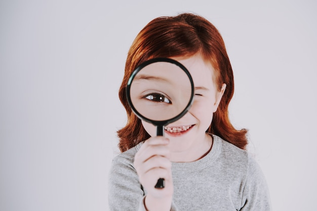 La niña mira la lupa, aumentando el tamaño del ojo.