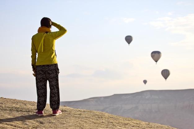 La niña mira el vuelo de globos en capadocia.