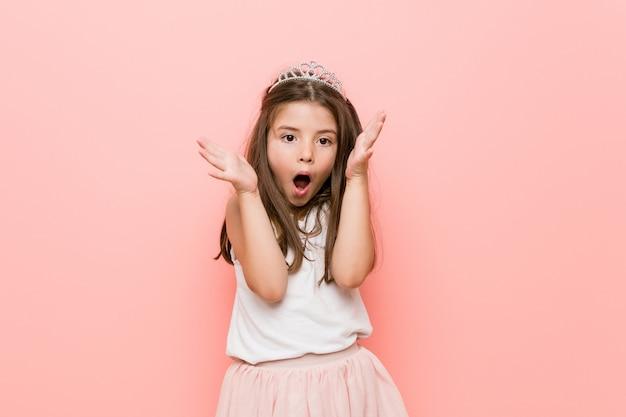 Niña con una mirada de princesa celebrando una victoria o éxito, él está sorprendido y conmocionado.