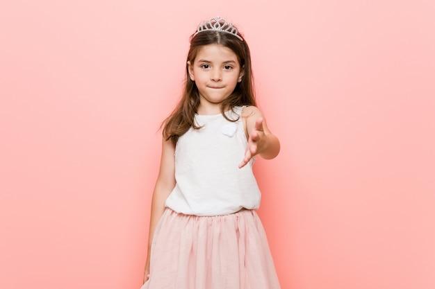 Niña con una mirada de princesa estirando la mano en gesto de saludo.