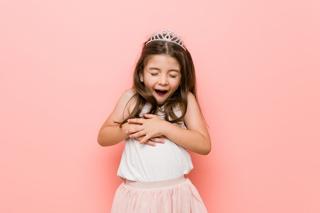 La niña con una mirada de princesa se ríe alegremente y se divierte manteniendo las manos sobre el estómago.