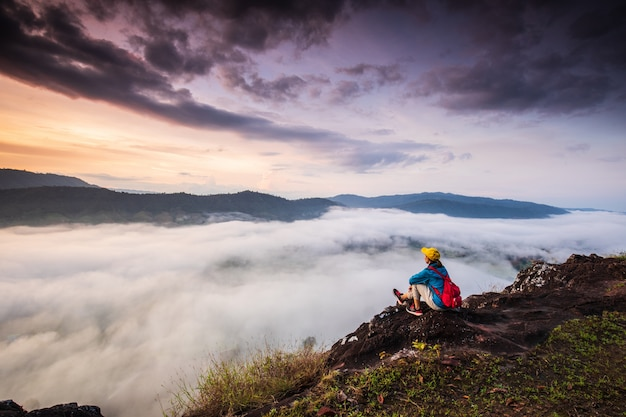 La niña está mirando al mar de niebla en alta montaña.