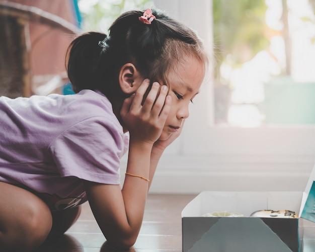 La niña está mirando la caja de donas, se pregunta si debería comerla.
