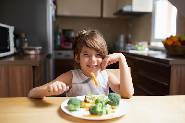 Niña mirando a la cámara mientras come verduras