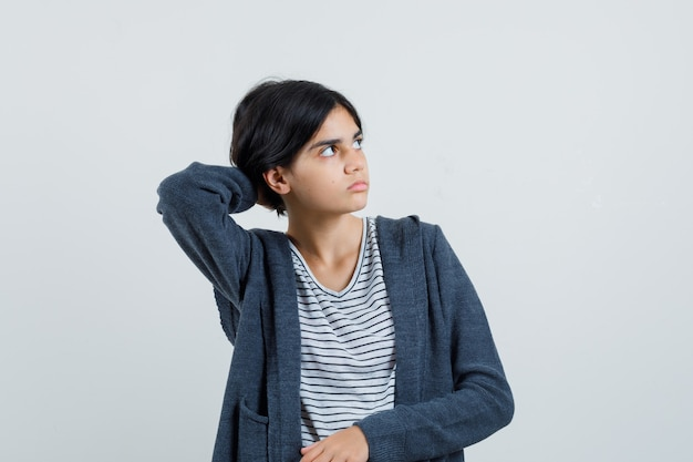 Niña mirando a un lado con la mano en el cuello en camiseta, chaqueta y mirando enfocado.