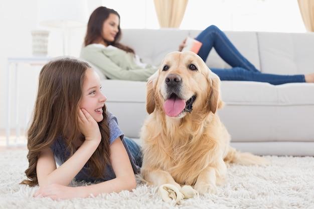 Niña mirando perro mientras está acostado en la alfombra