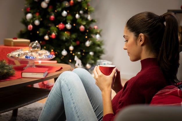 Niña mirando una taza con un fondo de navidad