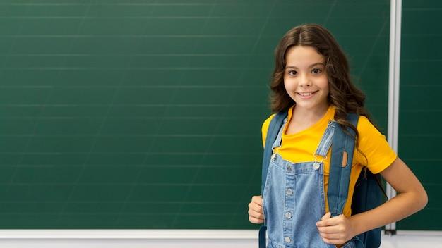 Niña con mochila en clase