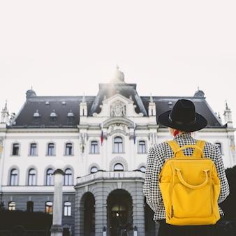 Niña con mochila en el fondo del edificio de la universidad de ljubljana que viven en eslovenia.