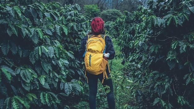 La niña con mochila está de pie y caminando en el jardín de café.