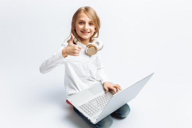 Niña moderna sentada con laptop, muestra clase, dedo arriba, lindo y hermoso