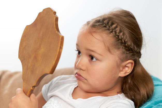 Niña molesta se mira en el espejo en un marco de madera