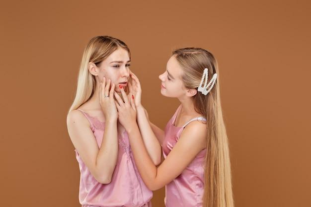 La niña está molesta por su acné y su amiga la calma y la apoya