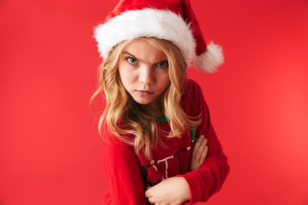 Niña molesta vistiendo traje de navidad que se encuentran aisladas, mirando