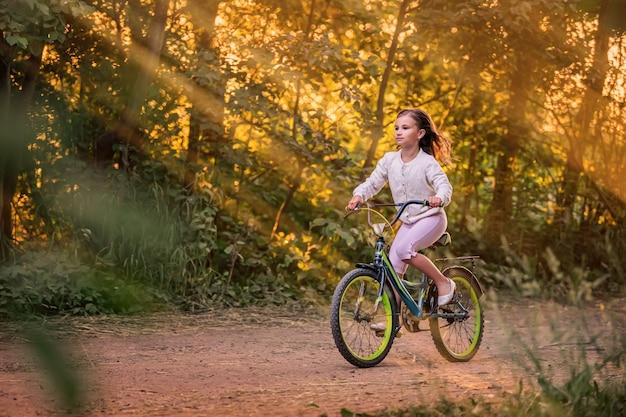 Niña montando en bicicleta por un camino rural en la naturaleza al atardecer