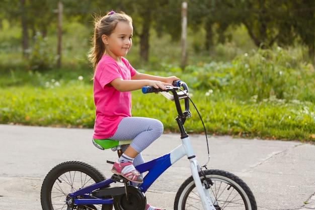 Niña montando bicicleta en el parque de la ciudad.
