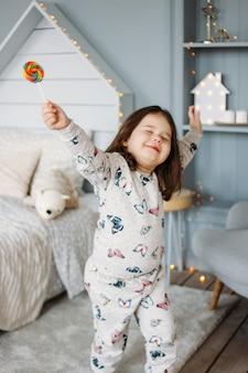 Niña morena divertida en pijama acogedor con lollipop en la habitación de los niños
