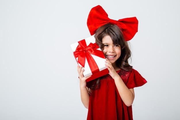 Niña morena con un gran lazo en la cabeza sostiene una caja de regalo en sus manos