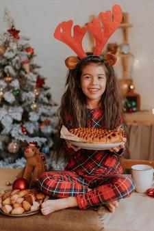 Niña morena en pijama rojo a cuadros con cuernos de ciervo en la cabeza está comiendo un pastel de navidad