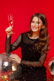 Niña morena sentada en un vestido negro y sostiene una copa de champán en sus manos
