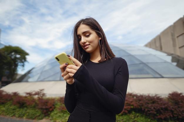 Niña morena usando su teléfono celular mientras explora una nueva ciudad